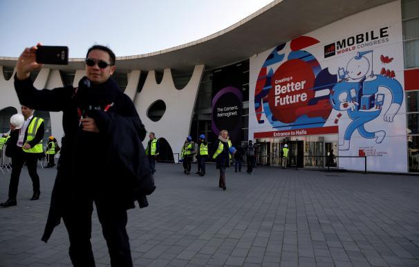 Un visitante se hace una foto ante la entrada de la Fira Gran Via donde a partir del lunes se celebra una nueva edición del MWC. EFE/Alberto Estevez