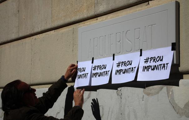 Una mujer coloca carteles a las puertas del Palacio Arzobispal de Tarragona durante la concentración llevada a cabo este sábado para protestar y expresar su rechazo a los abusos a menores, presuntamente cometidos por capellanes. EFE/Jaume Sellart