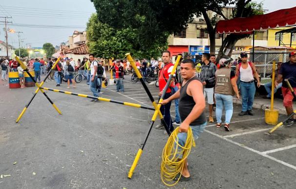 Un grupo de personas desarman las barreras de seguridad instaladas por la Guardia Nacional Bolivariana (GNB) que bloquean el paso sobre el río Táchira (EFE/HECTOR PEREIRA)