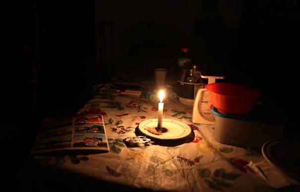 Una mesa iluminada por una vela durante el apagón eléctrico en Caracas