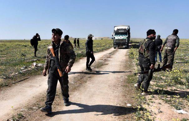 Combatientes de las Fuerzas Democráticas Sirias (SDF), observan camiones cargados con desplazados cerca de la ciudad de Baghouz (EFE / EPA / MURTAJA LATEEF).