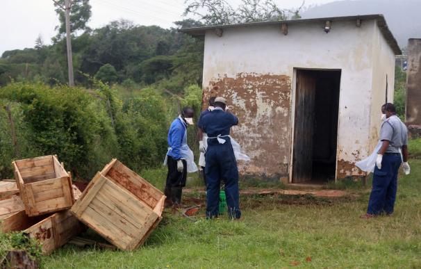 Personal sanitario y un oficial de policía se preparan para desinfectar los ataúdes temporales de los niños en las afueras de un depósito de cadáveres en el hospital del distrito rural de Chimanimani (EFE)