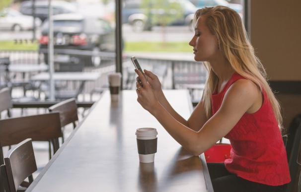 Una mujer toma café mientras mira el móvil