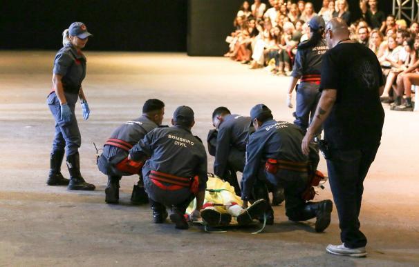 Bomberos auxilian al modelo Tales Cotta este sábado durante un desfile de la Semana de la Moda en Sao Paulo (Brasil). EFE