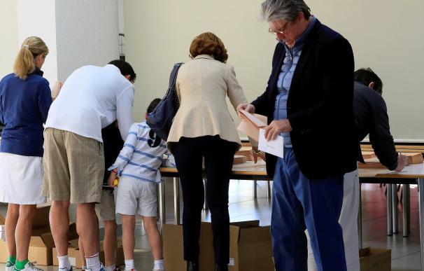 Varios ciudadanos recogen sus papeletas en el Colegio Base de La Moraleja