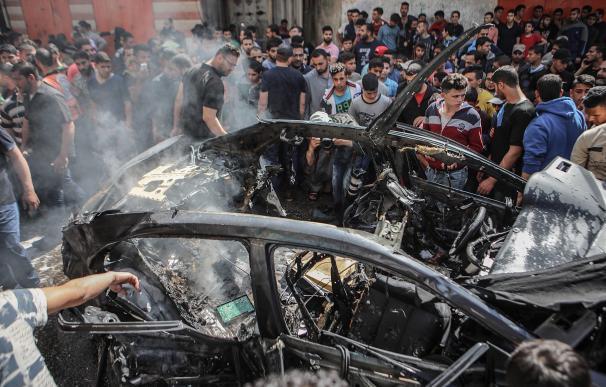 Palestinos inspeccionan el automóvil destruido del miembro de Hamas