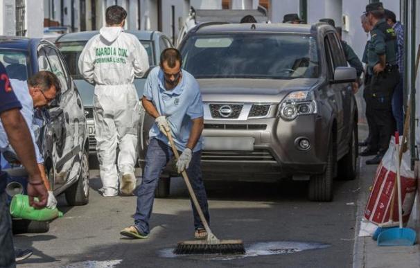 Varios operarios limpian la sangre de la puerta del domicilio donde el presunto asesino fue detenido. /RAÚL CARO  EFE