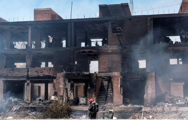 Un bombero trabaja en las labores de extinción del incendio con varias explosiones, originado en un edificio okupado del barrio de Es Viver de Ibiza