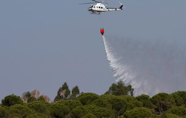 Un helicóptero de extinción de incendios trabaja en el Paraje de Fuente de la Corcha, en el término municipal de Beas (Huelva). /EFE