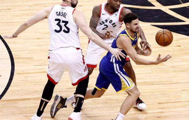 Klay Thompson (d) hace malabares con un balón mientras el delantero de los Toronto Raptors Kawhi Leonard (c) y el centro de los Toronto Raptors Marc Gasol (i) de España defienden en el juego de baloncesto de las finales de la NBA entre los Golden State Wa