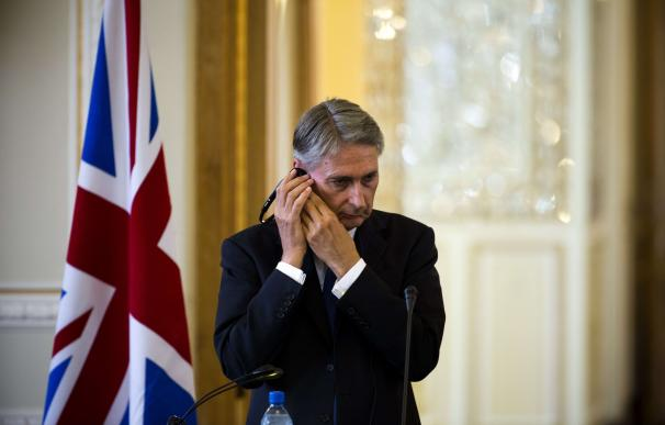 British Foreign Minister Philip Hammond holds his
