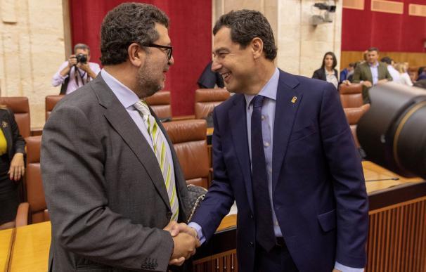 El presidente andaluz, Juanma Moreno, saluda al diputado de Vox, Francisco Serrano (i), al comienzo del pleno del Parlamento de Andalucía hoy en Sevilla, que debate la convalidación o derogación del decreto ley del Gobierno autonómico con el que se aprobó
