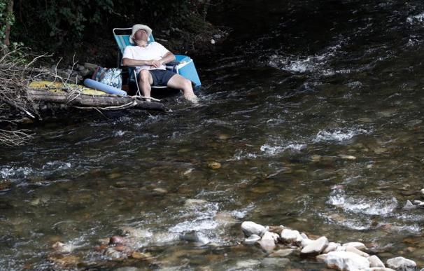 Ola de calor, señor sentado en una hamaca junto al río