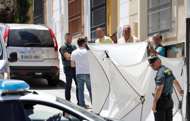 Agentes de la Guardia Civil despliegan una lona para tapar el traslado del cuerpo sin vida de la mujer de 42 años asesinada