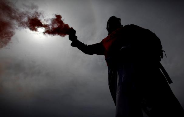 Un trabajador de Alcoa con un bote de humo en la cabecera de la manifestación de A Coruña. /EFE/Cabalar