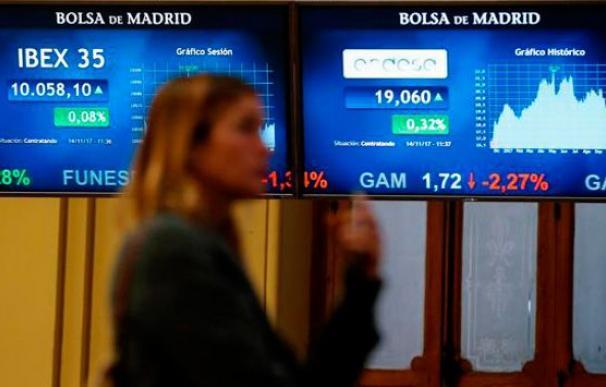 Imagen de una mujer frente a los paneles del Ibex 35. / EFE