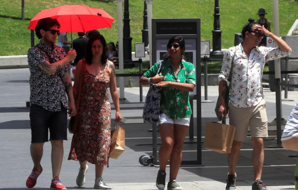 Varias personas intentan protegerse del calor en las inmediaciones del Museo del Prado. /EFE