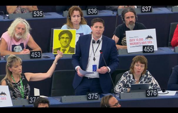 El eurodiputado irlandés Matt Carthy interviene reivindicando a Puigdemont mientras Martina Anderson sujeta un cartel con su cara.