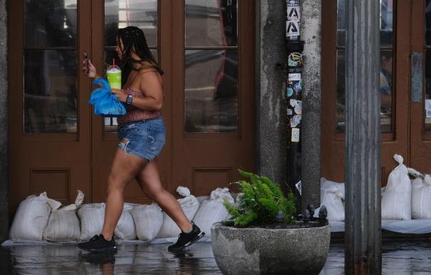 Una mujer camina por una tienda del Barrio Francés rodeada de bolsas de arena cuando se acerca la tormenta tropical Barry a Nueva Orleans, Louisiana. /EFE