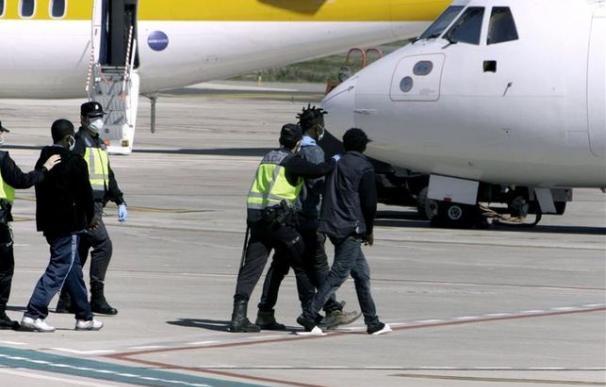 Agentes de la Policía Nacional trasladan hasta el avión a un grupo de inmigrantes desde Melilla a la península (imagen de archivo). /EFE