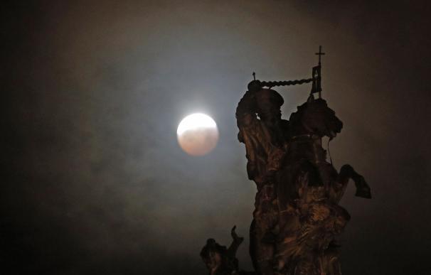 La luna llena durante la fase final del eclipse total, sobre una figura ecuestre del Apóstol Santiago en la Plaza del Obradoiro