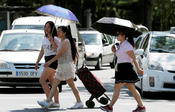 Tres mujeres se protegen del sol y del calor con sombrillas en Valencia. /EFE/Kai Försterling
