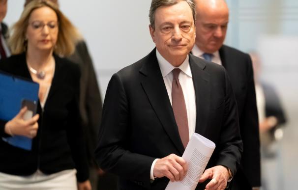 Draghi camina hacia la rueda de prensa escoltado por Guindos.