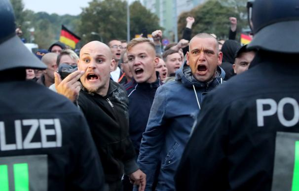 Manifestantes de ultraderecha gritan detrás de una fila de policías en Chemnitz, Alemania, el 1 de septiembre de 2018. (EFE / EPA / MARTIN DIVISEK)