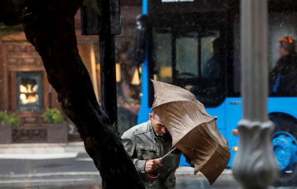 Un hombre camina bajo la lluvia en San Sebastián. EFE/Javier Etxezarreta