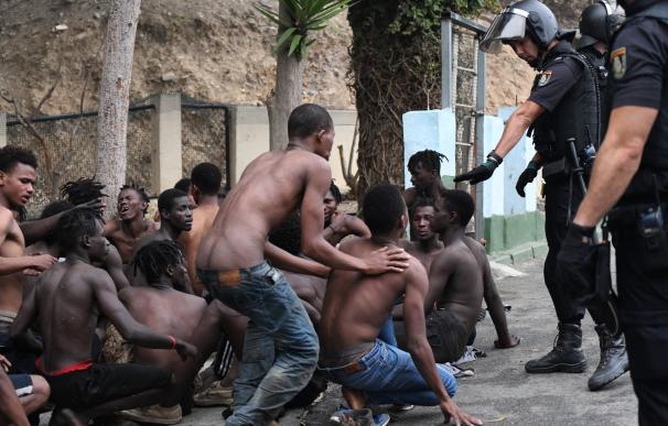 Imagen de inmigrantes y efectivos policiales ante el salto masivo a la valla de Ceuta el 30 de agosto