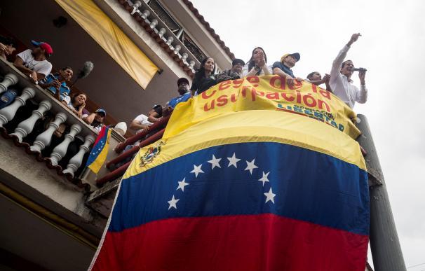 El jefe del Parlamento, Juan Guaidó (d-arriba), saluda a ciudadanos durante una visita este sábado, a la localidad de Charallave (Venezuela). /EFE