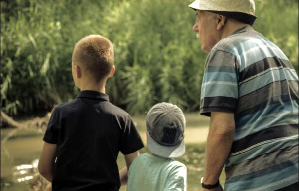 Fotografía de un pensionista con sus dos nietos.
