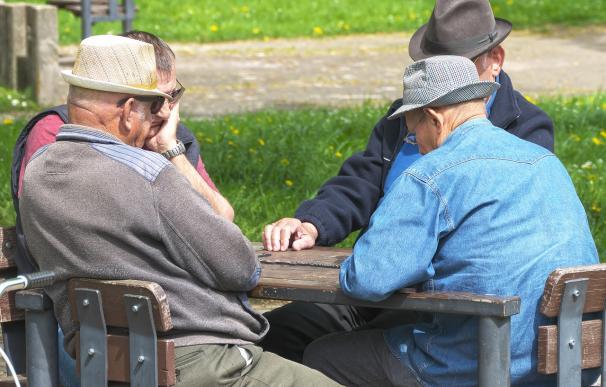 Fotografía de varios jubilados jugando al dominó.