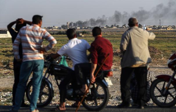 La gente mira la frontera turco-siria mientras el humo se eleva tras el bombardeo de las fuerzas turcas en la ciudad de Tal Abyad. /EFE