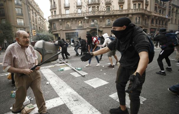 Un anciano se enfrenta a uno de los manifestantes en Barcelona. / EFE/Jesús Diges