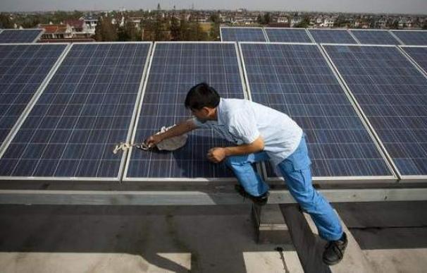 Un trabajador limpia una placa solar en la azotea de un edificio. EFE