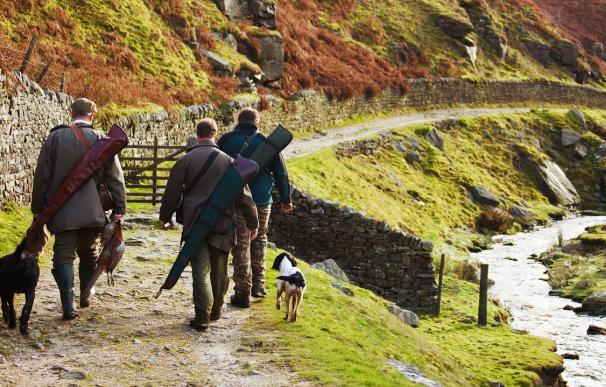 Fotografía de cazadores junto a sus perros de caza.
