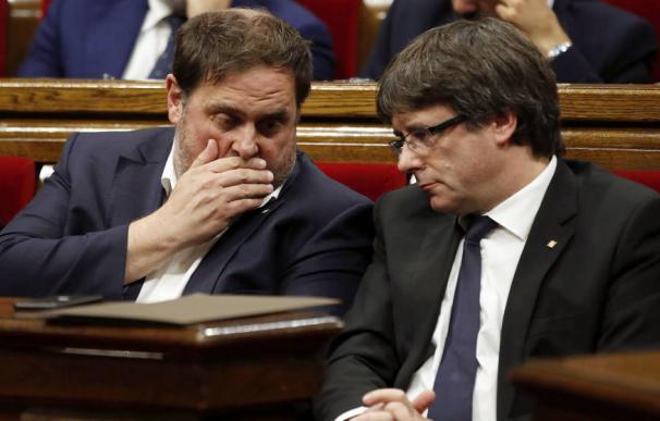 El expresidente de la Generalitat Carles Puigdemont (d) y el exvicepresidente Oriol Junqueras (i) en el Parlament. (EFE)