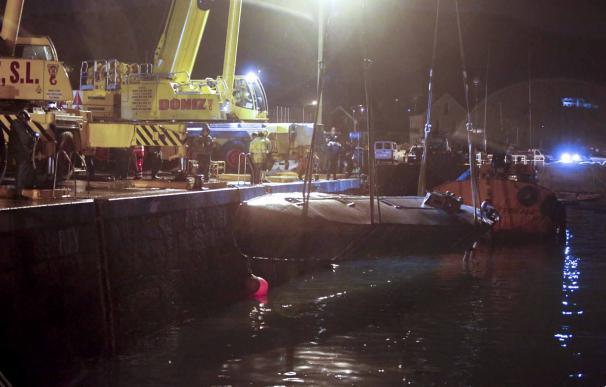 Dos grandes grúas izan desde el muelle de Aldán, en Cangas (Pontevedra), el 'narcosubmarino' localizado en Punta Couso el 23 de noviembre.