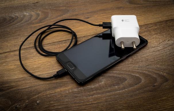 Fotografía de un móvil con su cargador.