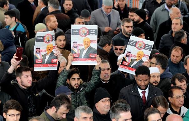 Hombres sostienen una imágenes del periodista opositor saudí Jamal Khashoggi mientras rezan en la mezquita Fatih, en Estambul (Turquía)