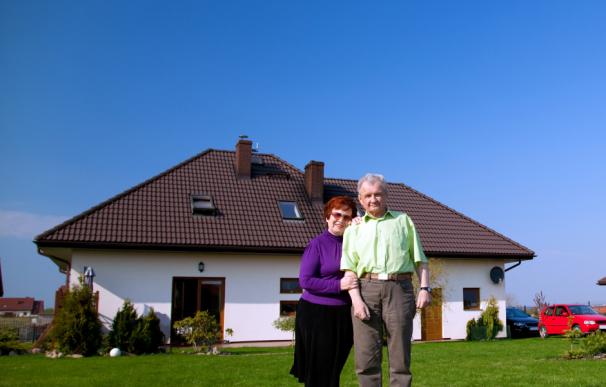 Fotografía de dos jubilados con una casa.