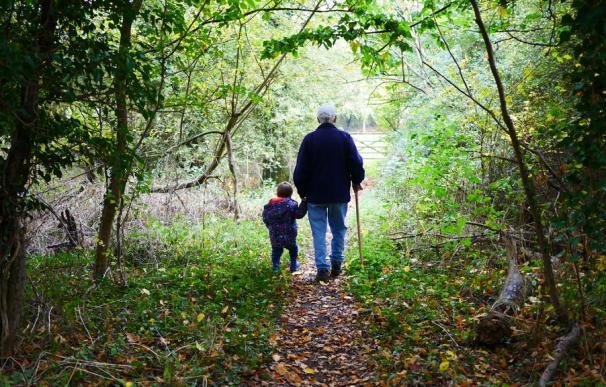 Fotografía de un abuelo jubilado paseando junto a su nieto.
