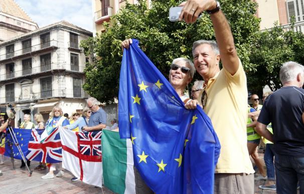 Una pareja se toma un selfie junto a la bandera de europea en Málaga durante una protesta contra el Brexit