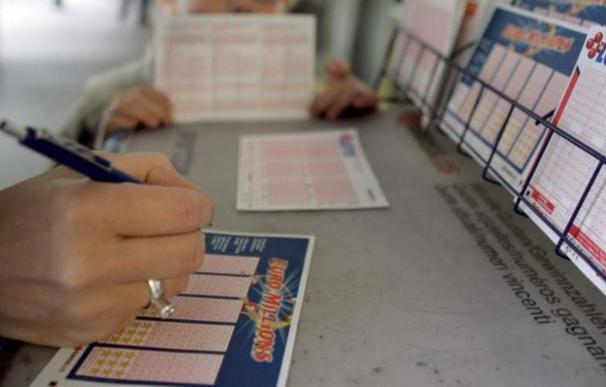 Una mujer marca los números en su participación del Euromillones. / EFE