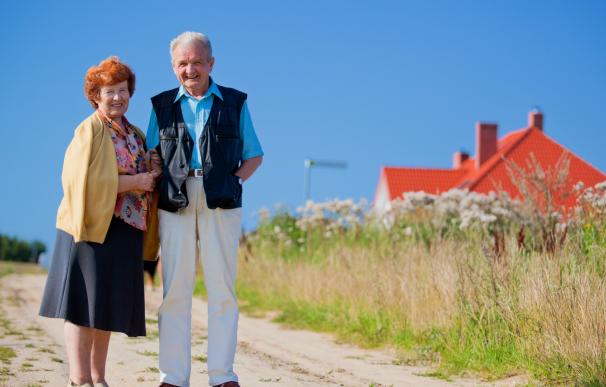 Fotografía de dos jubilados frenta a su casa.