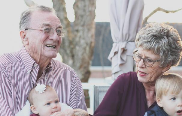 Fotografía de dos jubilados pensionistas junto a sus nietos.