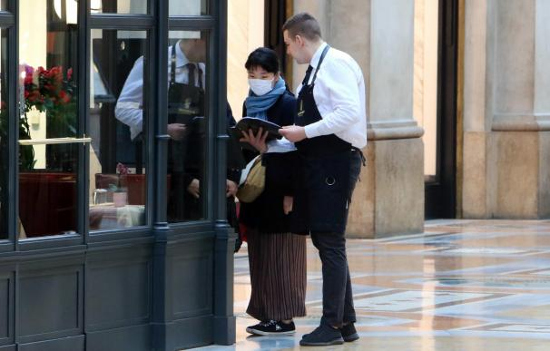Una turista asiática con una máscara protectora revisa el menú de uno de los restaurantes en la galería central Vittorio Emanuele en Milán, Italia. /EFE/EPA/Paolo Salmoirago