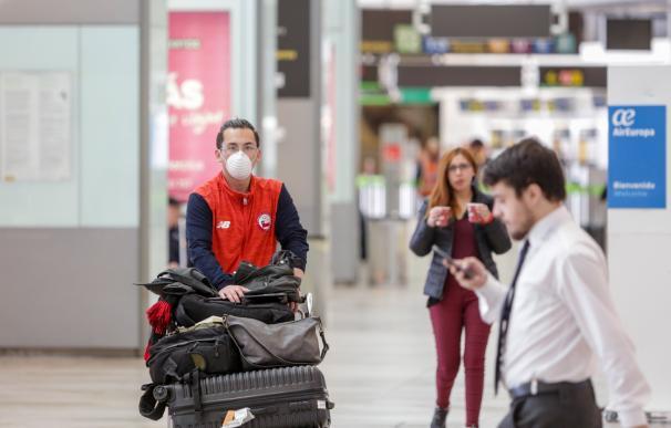 Un operario con mascarilla traslada maletas en el aeropuerto de Barajas, casi vacío