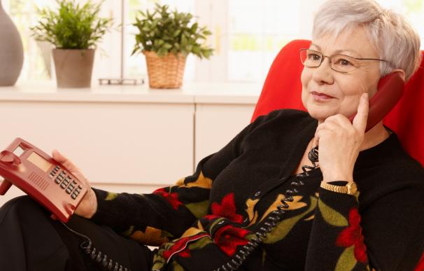 Fotografía de una jubilada haciendo una gestión con el banco por teléfono.